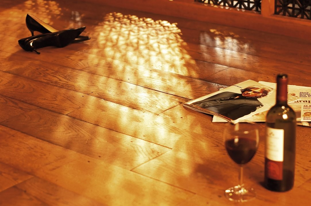 Location shot of oak floor with bottle of wine and ladies shoes