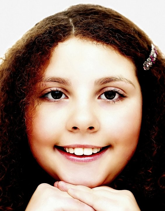 Fashion close up of young girl with curly hair resting her head on her hands, smiling