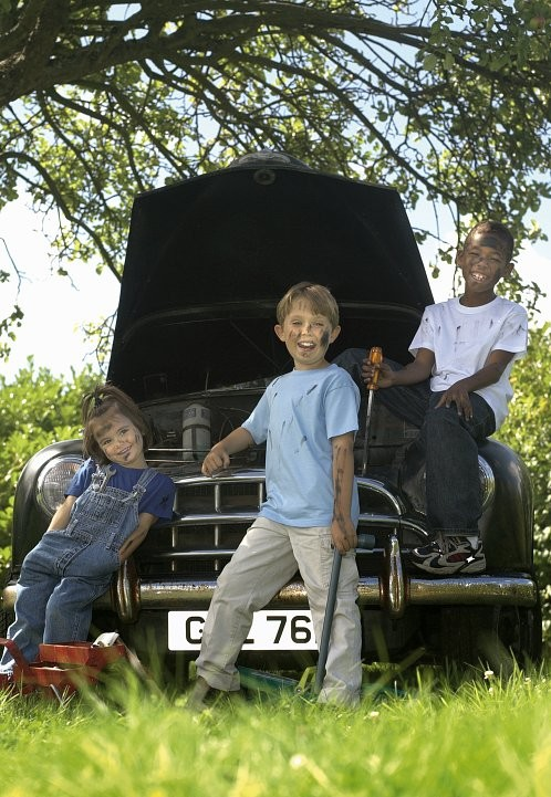 Fashion. Three young children working as mechanics on a classic car