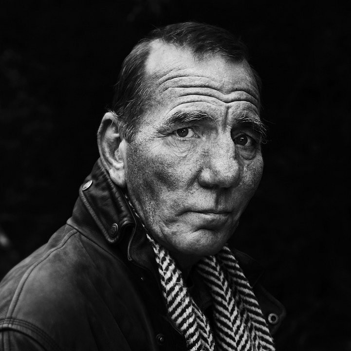 Close up portrait of actor Pete Postlethwaite in black and white.